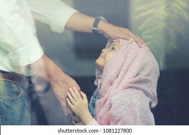 5 years old Muslim Asian girl  in traditional clothing greeting to elders,her father by touch his hand and smiling.The candid scene through the outside window.Concept of family bonding and supporting.