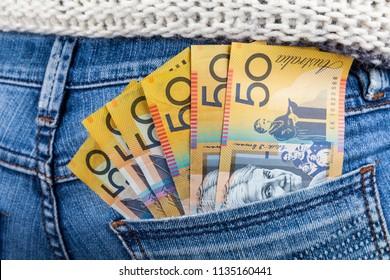 50 AUD bills in fan shape placed in female jeans back pocket closeup - minimum wage concept