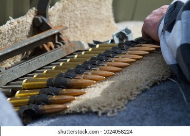 .50 caliber bullets being loaded into a belt for a machine gun