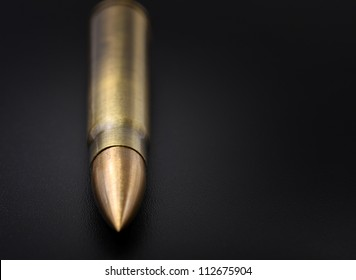50 caliber rifle cartridge with bullet on black background close up