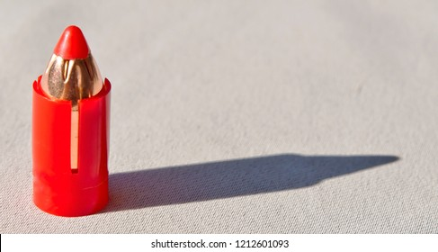 A 50 caliber sabot bullet for a muzzle loader rifle in a plastic red casing casting a shadow on a white background