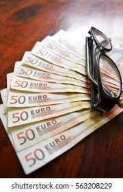 50 euro banknotes with glasses on wood table