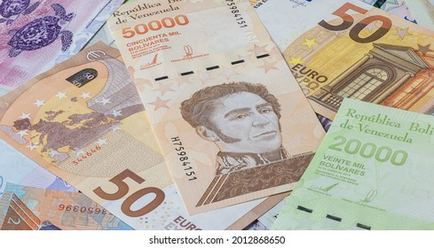 50 Euro in a big pile of Bolivar banknotes. Many Bolivares bills lie on top of each other. Bunch of money of the almost bankrupt country of Venezuela . Currency of the republic Venezuela between Euros