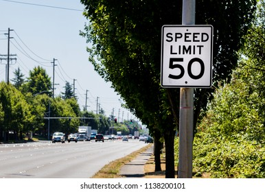 50 mph speed limit sign on post with a road and tree with bushes