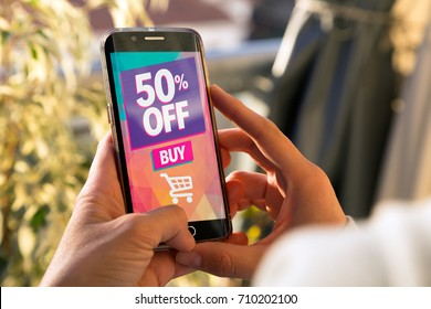 50% OFF Sale. Girl holding a smartphone with a 50% discount advertising on the screen. Marketing, ecommerce, cell phone publicity.