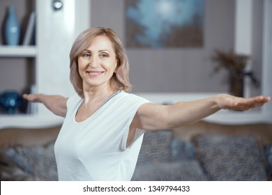 A 50 Year Old Blond Woman Doing Yoga at Home. She is in a Good Mood. Yoga is Her Favorite Activity. Close Up Shot.