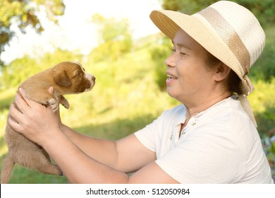 50 year-old Southeast Asian country woman is looking brown puppy dog in hand with blurry focus nature background. happy with life , enjoy and relax concept.  lens flare sunshine effect.