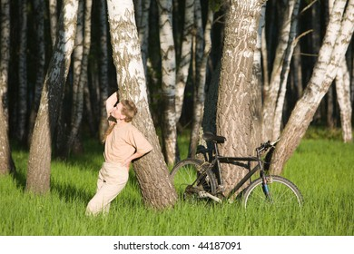 50 years old woman with bicycle in  birch forest at summer