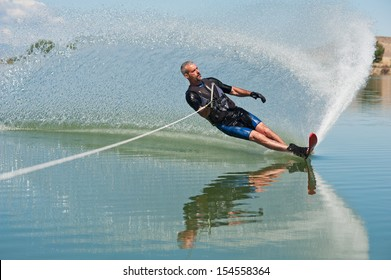 "A 50 yr. old man slalom waterskiing on Sweitzer Lake in Delta, Colorado. He is carving the water with his ski as he makes a turn, creating a ""rooster tail"" of water."