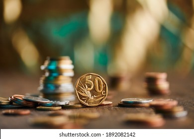 A 50 ZAR cents coin standing up on a brown wood surface and gold and blue background with other currencies coins surrounding and towering up in stacks.