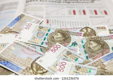500 PLN banknotes on financial newspaper with bar graphs and charts