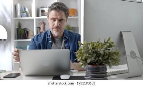 Geschäftsmann der 50er Jahre mit grauem Haar, der von zu Hause aus arbeitet. Mann im Gelegenheitssitzend am Schreibtisch mit Laptop-Computer, Business Manager online im Home Office.