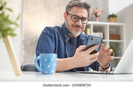 50s man checking news on phone at home. Confident happy smiling.