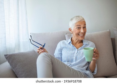 50-year-old woman at home drinking tea. Cosy looking senior woman at home with hot drink. Happy vivacious middle-aged blond woman holding a cup of tea or coffee looking at the camera