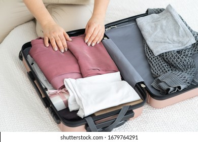 A 50-year-old woman parses a suitcase and puts off the trip. Quarantine. Coronavirus. Stop traveling. Stay at home. Put things in order. Take things away. The order in wardrobe.