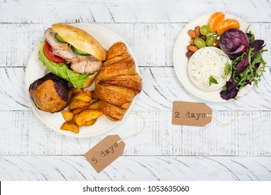 5:2 fasting diet concept. Two plates with unhealthy and balanced meal. Healthy choice of food on white wooden table. Copy space