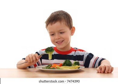 5-6 years old boy and plate of cooked vegetables isolated on white /focus on broccoli/