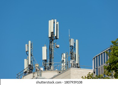 5G and 4G mobile phone antennas installed on the rooftop of a building. Blue sky