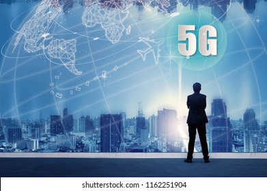 5G network wireless systems and internet of things with successful businessman standing on top of building and looking through Cityscape Skyline Night Light, Connect global wireless devices.