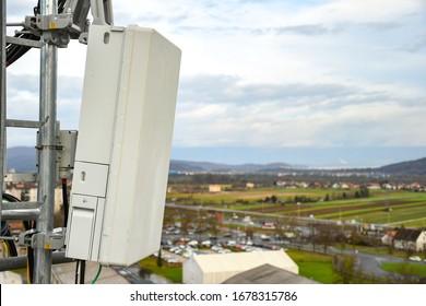 Antenne de réseau de télécommunications radio 5G montée sur un pôle métallique fournissant de fortes ondes de signal depuis le sommet du toit à travers la grande ville