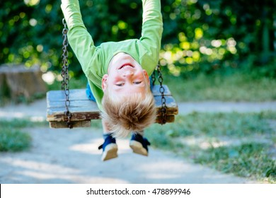 5-year old boy upside down on a wooden swing having fun in summer