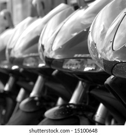 6 black motorbikes parked in a row, focus is on the front bike