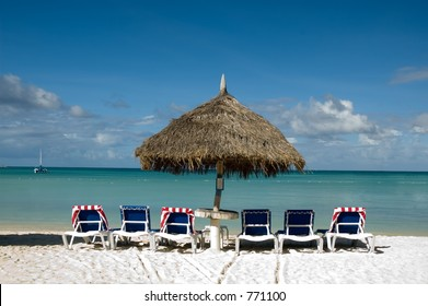 6 chairs under one palapa umbrella on the beach