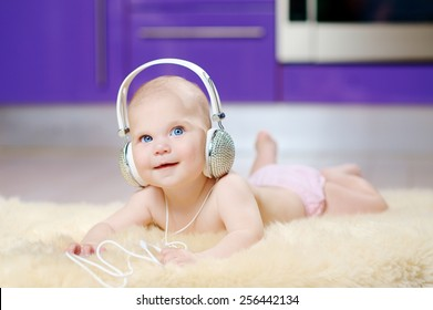 6 month baby photo shoot in white headphones with crystals on a beige fur on the floor