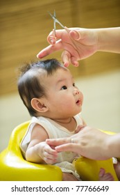 6 month old Asian baby girl having a haircut, while sitting in a yellow chair