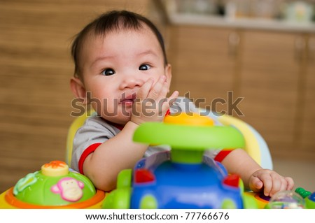 6 month old Asian baby girl chewing her fingers while sitting in a walker Month Old Baby Girl Stock Photo (Edit Now) 77766676