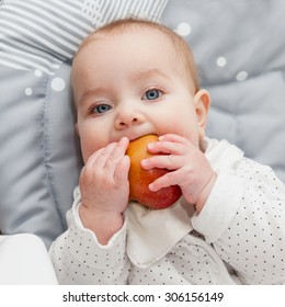 6 month old baby trying his first fruit: apple. Baby lead weaning. First food. Baby looking straight at the camera. Selective focus on baby head.