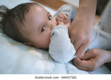 6 month old newborn mixed race Asian Caucasian boy being dressed by his Asian mother at home in a bedroom. Natural indoor lighting.