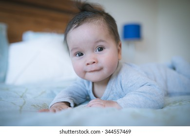 6 month old newborn mixed race Asian Caucasian boy plays on a bed. Natural indoor lighting. Cool tones