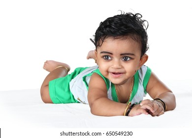 6 months indian baby laying on the white bed along with white background.