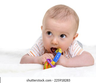 6 months old baby boy playing with his teether or toy