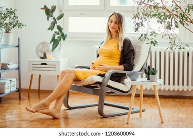 6 months pregnant young woman holding her belly and sitting on rocking chair