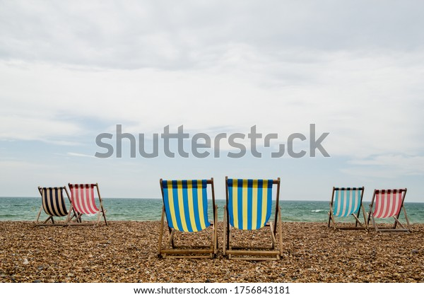 6 stripy deck chairs on an empty shingle beach on an overcast day. Taken in Brighton, England, UK