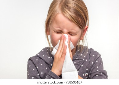 6 year old girl sneezing into a white tissue isolated on white