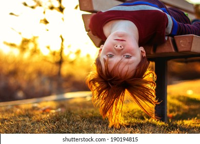 6 year old redheaded boy hanging upside down from a park bench--image taken outdoors using natural light (Sparks, Nevada, USA)