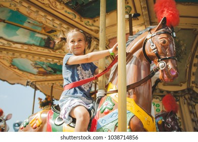 6 years girl on the toy horse in the amusement park