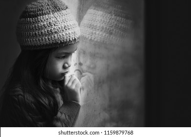 6 years old Asian girl sad by the window in winter red sweater and knitted hat.Cold weather make condensation on window glass,girl draw sad face on it.Concept of sad child.Black and white color tone.