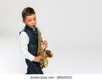 6 years old boy plays saxophone at studio