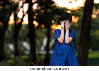6 years old mixed race Asian girl in the park while sun .Girl hide or cover her face with her hands.She may playing hide and seek or may crying.