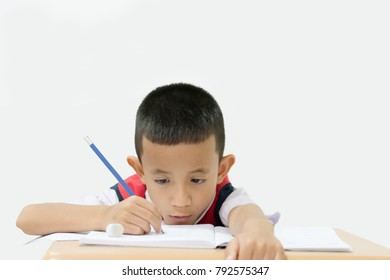 A 6 years olds kindergarten scool boy is holding blue pencil and concentrated to writing.