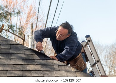 60 years old roofer putting asphalt roof shingles on a house structure