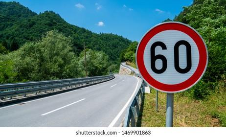 60kmh speed limit sign near a calm road running through a forest
