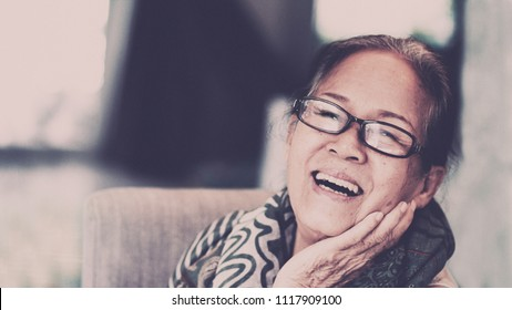 60s or 70s  Asian elderly woman wearing eyeglasses rest her chin on her hands.She looks happy and peaceful mind,looking to camera and smiling.Happy elderly concept.Film color tone.