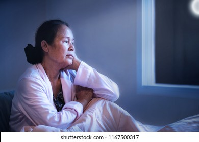 60s or 70s Asian senior woman having sleep disorder, sitting in bed look sad.Lonely grandmother have Difficulty falling asleep. Waking up often during the night and having trouble going back to sleep.