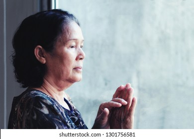 60S or 70s  years old Asian elderly woman sad by the window.Granny touch the window glass and looking outside,she may worried or thinking of something or waiting for someone.Concept of lonely elderly.