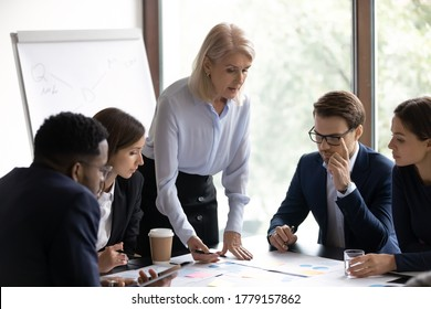 60s businesswoman project leader and diverse millennial workmates learn data of financial report during group meeting in boardroom. Do analysis and research, engagement in teamwork, brainstorm concept